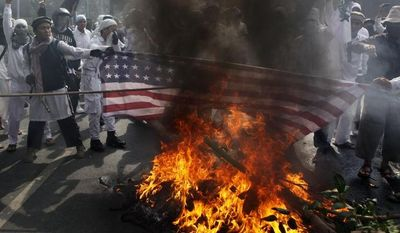 "Muslim protesters burn a U.S. flag during a demonstration against the American-made film ""Innocence of Muslims,"" which ridicules Islam and depicts the Prophet Muhammad as a fraud, a womanizer and a madman, outside the U.S. Embassy in Jakarta, Indonesia, on Monday, Sept. 17, 2012. (AP Photo/Dita Alangkara)"
