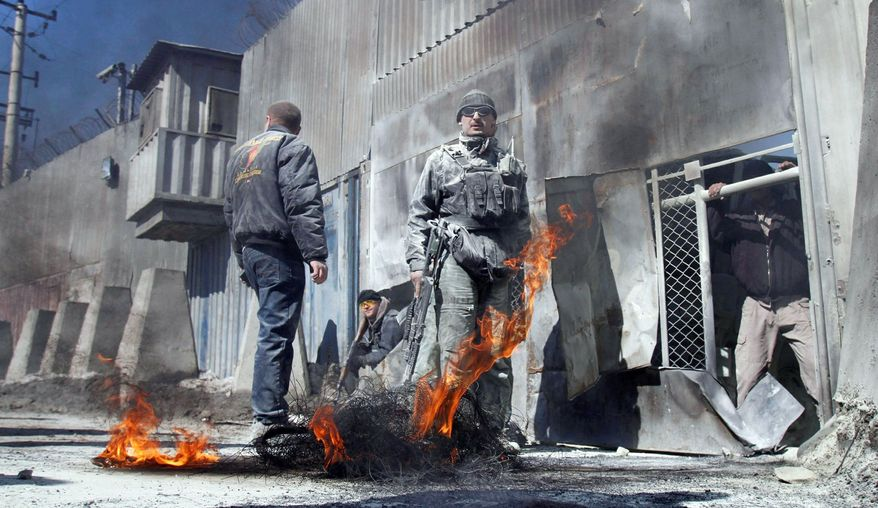 Afghan security guards stand by the remnants of a tire burned during an anti-U.S. demonstration in Kabul, Afghanistan, in February. In recent years, allied troops lived and trained with their Afghan counterparts. But killings of allied troops took a toll in trust. The Pentagon said Tuesday that it has stopped training Afghan troops and working with them below battalion level. (Associated Press)