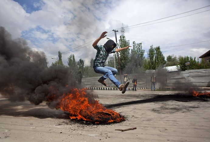 A Kashmiri Muslim protester jumps over a burning tire set up as a roadblock in Srinagar, India, on Tuesday, Sept. 18, 2012, during a protest against a film ridiculing Isla