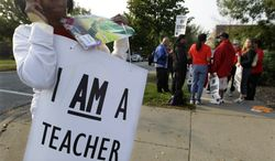 ** FILE ** A handful of teachers picket Sept. 17, 2012, outside Shoop Elementary School in Chicago, as a strike by Chicago Teachers Union members headed into its second week. (Associated Press)