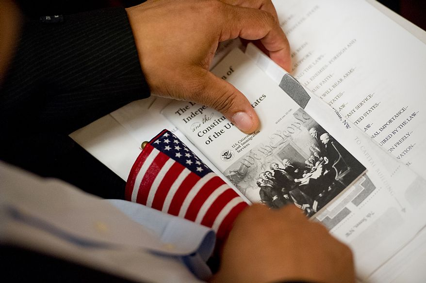 A petitioner holds a pamphlet on the Declaration of Independence and the Constitution of the United states as he and 224 others wait to be sworn in as U.S. citizens on Sept. 17, 2012, at the National Archives Building in Washington, during a naturalization ceremony to commemorate the 225th anniversary of the signing of the U.S. Constitution. (Andrew Harnik/The Washington Times)