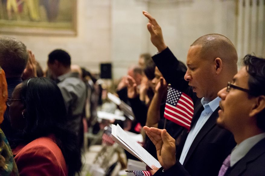Pablo Mendez, originally from the Dominican Republic, raises his hand as he and 224 others were sworn in as U.S. citizens on Sept. 17, 2012, at the National Archives Building in Washington, during a naturalization ceremony to commemorate the 225th anniversary of the signing of the U.S. Constitution. (Andrew Harnik/The Washington Times)