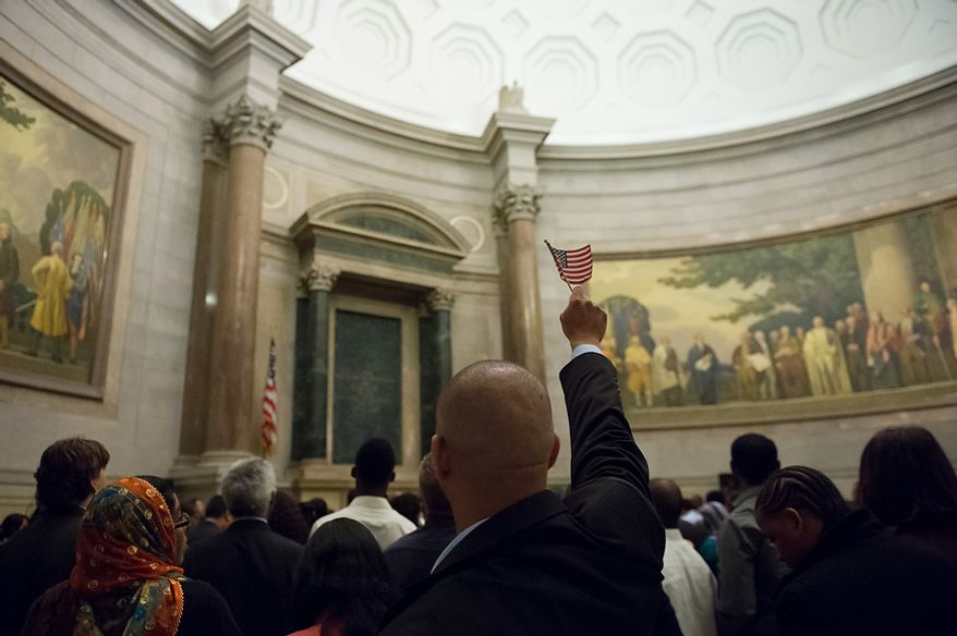 Pablo Mendez, originally from the Dominican Republic, raises an American flag as his name is called on Sept. 17, 2012, at the National Archives Building in Washington, during a naturalization ceremony to commemorate the 225th anniversary of the signing of the U.S. Constitution. (Andrew Harnik/The Washington Times)