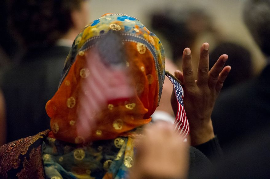 A petitioner holds an American flag in her hand as she and 224 others were sworn in as U.S. citizens on Sept. 17, 2012, at the National Archives Building in Washington, during a naturalization ceremony to commemorate the 225th anniversary of the signing of the U.S. Constitution. (Andrew Harnik/The Washington Times)