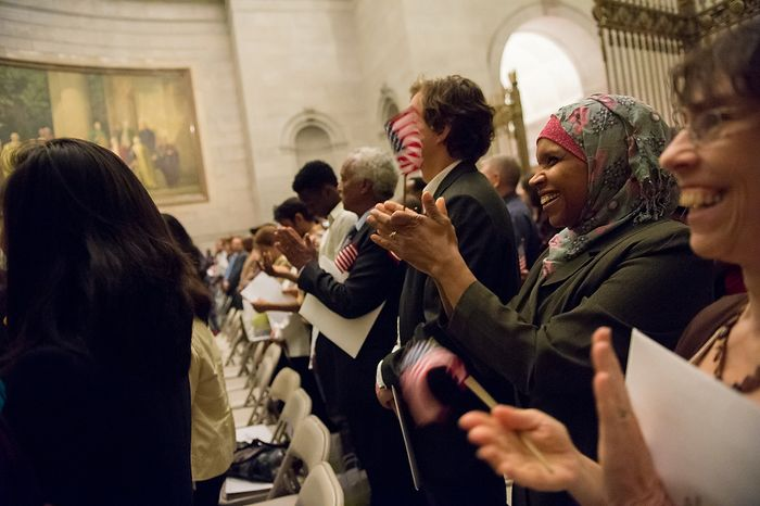 Mahjouba Elhaloui (second from right), originally from Morocco, and Natalie Donn White (right), originally from Canada, applaud with 223 other newly sworn-in U.S. citizens on Sept. 17, 2012, at the National Archives Building in Washington. The ceremony commemorated the 225th anniversary of the signing of the U.S. Constitution. (Andrew Harnik/The Washington Times)