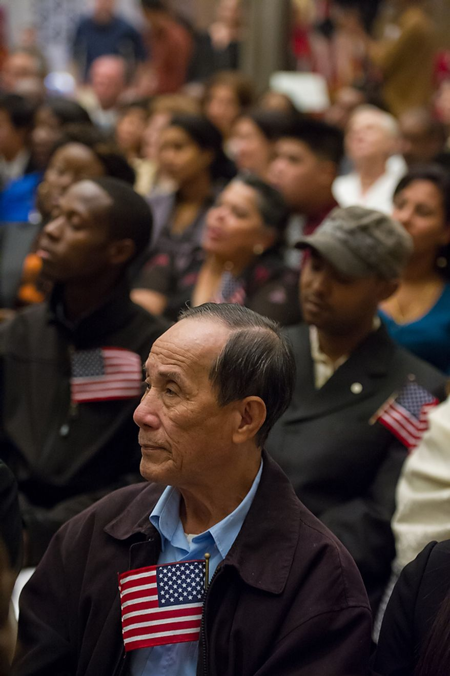 Duc Nguyen (center), originally from Vietnam, listens along with 224 other newly sworn-in U.S. citizens on Sept. 17, 2012, at the National Archives Building in Washington, during a naturalization ceremony to commemorate the 225th anniversary of the signing of the U.S. Constitution. (Andrew Harnik/The Washington Times)
