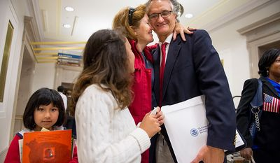 French native and D.C. resident Dominique Bagnato (right) is greeted by his wife, Tesa Conlin, and their two daughters Mila Bagnato-Conlin (left), 7, and Bliss Bagnato-Conlin, 11, after he and 224 others were sworn in as U.S. citizens on Sept. 17, 2012, at the National Archives Building in Washington, during a naturalization ceremony to commemorate the 225th anniversary of the signing of the U.S. Constitution. (Andrew Harnik/The Washington Times)