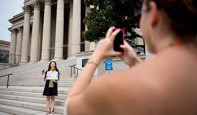 Margaret Massimo of New York photographs her former college roommate Masako Chen, originally from China, as she poses with her certificate of citizenship on Sept. 17, 2012, at the National Archives Building in Washington, after a naturalization ceremony to commemorate the 225th anniversary of the signing of the U.S. Constitution. (Andrew Harnik/The Washington Times)