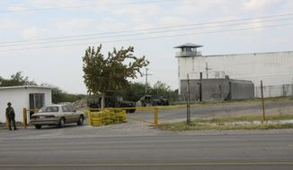 Mexican army soldiers guard an entrance to the prison in the city of Piedras Negras, Mexico, Tuesday, Sept. 18, 2012. Federal police units and Mexican troops, including 70 members of an elite military special forces unit, are searching for inmates who fled the prison in this city across the border from Eagle Pass, Texas. They escaped allegedly through a tunnel 21 feet long and 4 feet in diameter on on Monday Sept. 17 and then cut their way through a chain link barrier and escaped onto a neighboring property. (AP Photo/Adriana Alvarado)