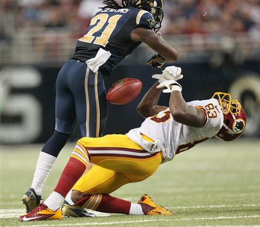 Fred Davis absorbs a helmet-to-helmet hit from Rams CB Janoris Jenkins / Associated Press