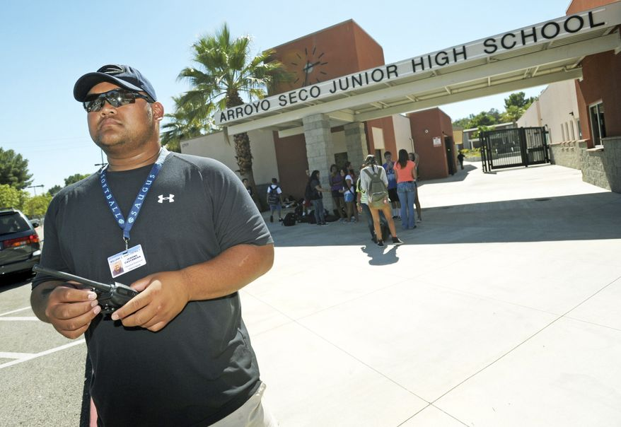 Campus supervisor Jerome Castaneda monitors the parking lot following dismissal at Arroyo Seco Junior High School in the Valencia neighborhood of Santa Clarita, Calif., on Tuesday, Sept. 18, 2012. Eric Yee, accused of posting comments on ESPN's website saying he was watching kids and wouldn't mind killing them, is in jail on $1 million bail after he was arrested at his home near the school for investigation of making terrorist threats, authorities said. (AP Photo/Santa Clarita Valley Signal, Jonathan Pobre)
