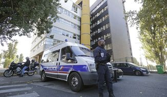 A policeman stands guard outside the headquarters of the satirical weekly Charlie Hebdo in Paris on Wednesday, Sept. 19, 2012, after the periodical published crude caricatures of the Prophet Muhammad. (AP Photo/Michel Euler) ** FILE **