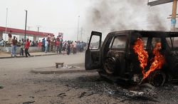 ** FILE ** Residents look on as a U.N. vehicle, set on fire by militant student supporters of Ivorian strongman Laurent Gbagbo, burns in the Riviera 2 neighborhood of Abidjan, Ivory Coast, on Thursday, Jan. 13, 2011. (AP Photo/Rebecca Blackwell)