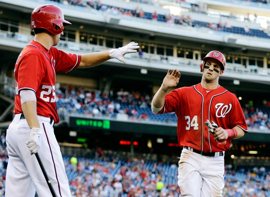 Washington Nationals' Bryce Harper (34)  celebrates scoring with Adam LaRoche (25) during the fifth inning of the first baseball game of a doubleheader against the Los Angeles Dodgers at Nationals Park, Wednesday, Sept. 19, 2012, in Washington. The Nationals won the first game 3-1. (AP Photo/Alex Brandon)
