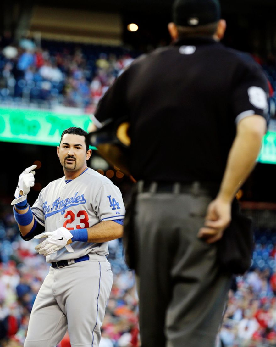 Los Angeles Dodgers' Adrian Gonzalez talks with umpire Brian Knight after he struck out during the seventh inning of the first baseball game of a doubleheader against the Washington Nationals at Nationals Park, Wednesday, Sept. 19, 2012, in Washington. The Nationals won the first game 3-1. (AP Photo/Alex Brandon)