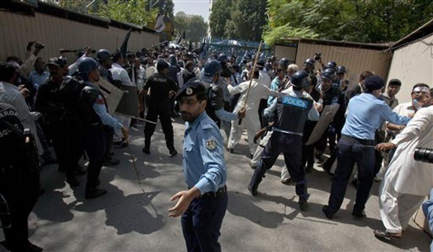 ** FILE ** Pakistani police officers scuffle with lawyers who try to enter the diplomatic enclave during a demonstration, near the area that houses the U.S. Embassy and other foreign missions, in Islamabad, Pakistan, Wednesday, Sept. 19, 2012. (AP Photo/Anjum Naveed)