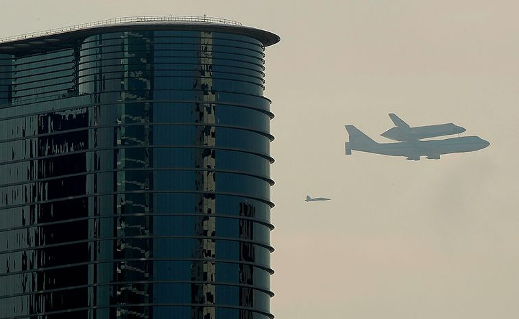 Space shuttle Endeavour sits atop the shuttle aircraft carrier as it flies over Houston, Wednesday, Sept. 19, 2012.  Endeavour is making a final trek across the country to the California Science Center in Los Angeles, where it will be permanently displayed. (AP Photo/Houston Chronicle, Mayra Beltran) MANDATORY CREDIT