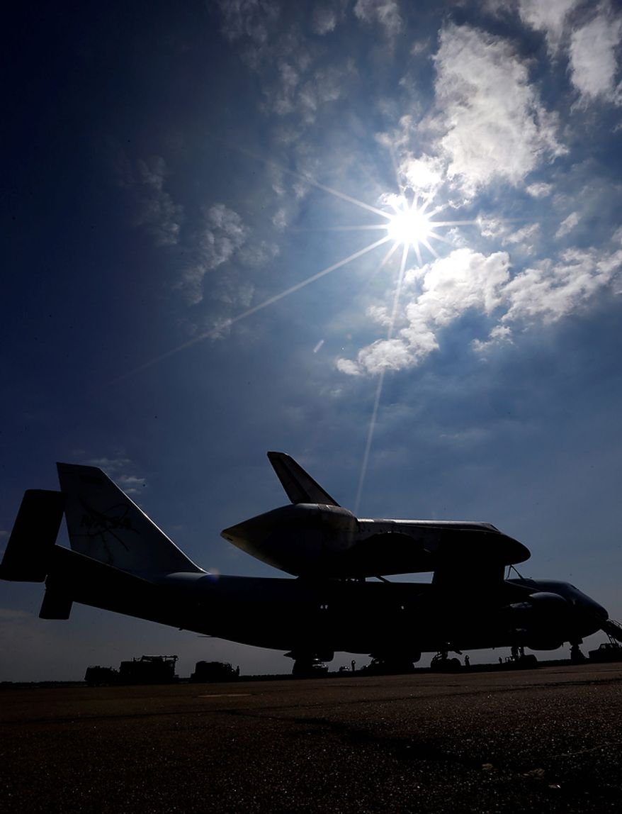 Space shuttle Endeavour sits atop the shuttle aircraft carrier after landing Wednesday, Sept. 19, 2012, at Ellington Field in Houston. Endeavour is making a final trek across the country to the California Science Center in Los Angeles, where it will be permanently displayed. (AP Photo/David J. Phillip