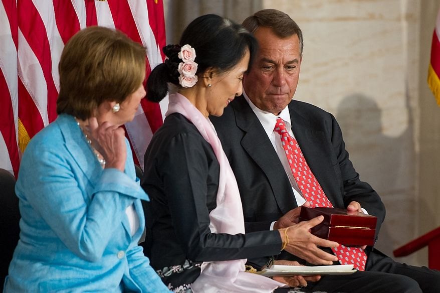 House Democratic Leader Nancy Pelosi (D-Calif.), left, looks on as Chairperson and General Secretary of the National League for Democracy Aung San Suu Kyi of Myanmar, also known as Burma, center, is handed the Congressional Gold Medal from Speaker of the House John Boehner (R-Ohio), right, in the Capitol rotunda, Washington, D.C., Wednesday, September 19, 2012. (Andrew Harnik/The Washington Times)