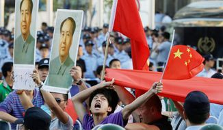A Chinese man shouts anti-Japan slogans in a crowd holding Chinese national flags and portraits of the late Communist leader Mao Zedong in front of the Japanese Embassy in Beijing on Tuesday. Mao died 36 years ago but is held in high esteem by those who think the current leadership pales in comparison. (Associated Press)