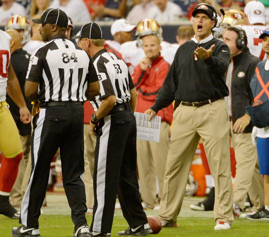 Jim Harbaugh, head coach of the San Francisco 49ers, disputes a pass-interference call against his team, as referees Derrick Rhone-Dunn (84) and Brad Hudspeth (53) confer in a preseason game against the Houston Texans in August. (Associated Press)