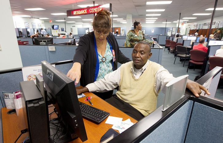 In this Friday, Sept. 7, 2012, photo, WorkForce One staffer Rose Capote-Marcus works with a client, Pen Osuji as he works on job applications at the Hollywood, Fla. unemployment office. The number of Americans seeking unemployment benefits fell by 3,000 last week to a seasonally adjusted 382,000, the Labor Department said on Thursday, Sept. 20, 2012. (AP Photo/J Pat Carter)