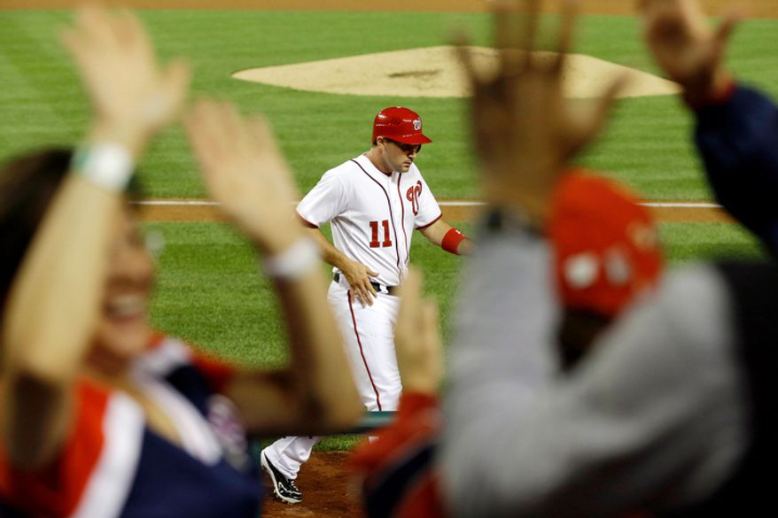 Fans cheer and high five as Washington Nationals Ryan Zimmerman (11) returns to the dugout after scoring against the Los Angeles Dodgers on a wild pitch during the third inning of a baseball game at Nationals Park. (AP Photo/Jacquelyn Martin)