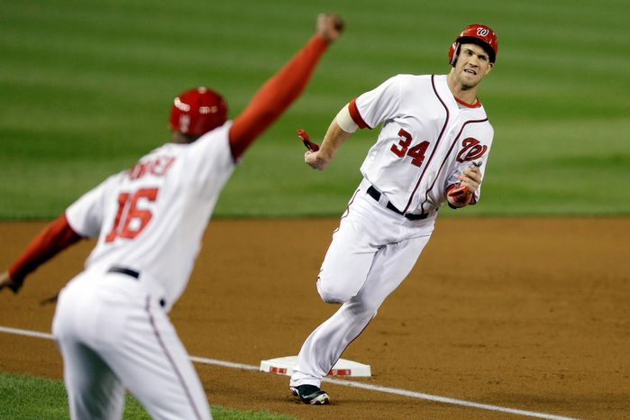 Washington Nationals Bryce Harper (34) rounds third base heading to home plate to score on a double from Ryan Zimmerman, against the Los Angeles Dodgers during the third inning of a baseball game at Nationals Park, in Washington. (AP Photo/J