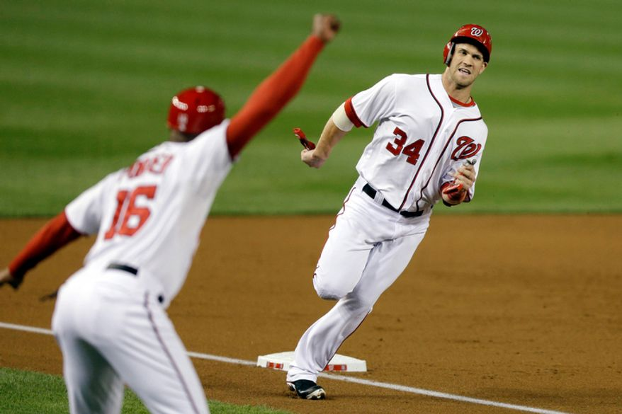 Washington Nationals Bryce Harper (34) rounds third base heading to home plate to score on a double from Ryan Zimmerman, against the Los Angeles Dodgers during the third inning of a baseball game at Nationals Park, in Washington. (AP Photo/Jacquelyn Martin)