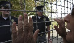 A Georgian woman speaks to police officers through a prison fence during a protest against prison abuse in Tbilisi, Georgia, on Thursday, Sept. 20, 2012. (AP Photo/Shakh Aivazov)