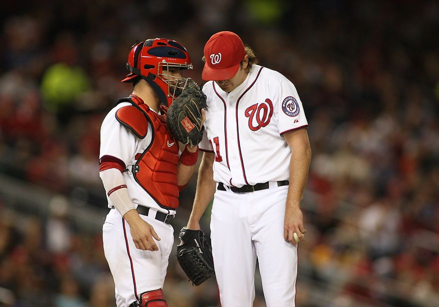 Washington Nationals catcher Jesus Flores (26) talks to starting pitcher John Lannan (31) during the second inning, Wednesday, Sept. 19, 2012, in Washington, DC. Washington Nationals lose to the Los Angeles Dodgers 6 to 7 in the second game of the doubleheader at National Park (Craig Bisacre/The Washington Times)