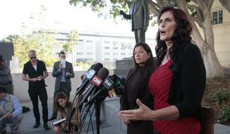 "Cindy Lee Garcia (right), one of the actresses in ""Innocence of Muslims,"" and attorney Cris Armenta hold a news conference before a hearing in Los Angeles Superior Court in Los Angeles on Thursday, Sept. 20, 2012. Miss Garcia asked a judge to issue an injunction demanding the 14-minute trailer for the anti-Islam film be pulled from YouTube. (AP Photo/Jason Redmond)"