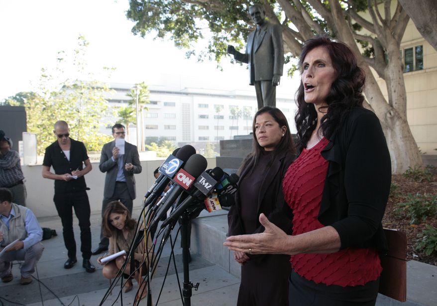 """Cindy Lee Garcia (right), one of the actresses in """"Innocence of Muslims,"""" and attorney Cris Armenta hold a news conference before a hearing in Los Angeles Superior Court in Los Angeles on Thursday, Sept. 20, 2012. Miss Garcia asked a judge to issue an injunction demanding the 14-minute trailer for the anti-Islam film be pulled from YouTube. (AP Photo/Jason Redmond)"""