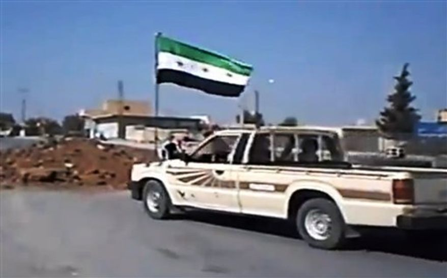 In this image taken from video obtained Wednesday, Sept. 19, 2012, from the Ugarit News, which has been authenticated based on its contents and other AP reporting, Free Syrian Army soldiers seize Ain al-Arous town in Raqqa, Syria, on Tuesday, Sept. 18, 2012. (AP Photo/Ugarit News via AP video)