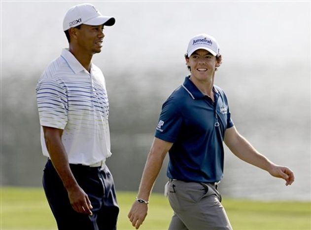 Tiger Woods, left, and Rory McIlroy, of Northern Ireland, walk up the fairway of the 17th hole during the first round at the Tour Championship golf tournament, Thursday, Sept. 20, 2012, in Atlanta. (AP Photo/David Goldman)