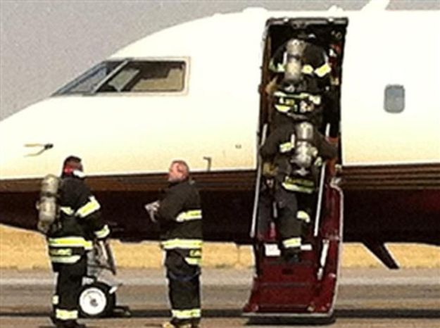 This photo released by Romney for President Press Secretary Andrea Saul via Twitter, firemen enter the plane carrying Anne Romney, wife of Republican Presidential nominee Mitt Romney, after the plane made an emergency landing Friday, Sept. 21, 20