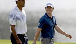 Tiger Woods (left) and Rory McIlroy walk up the fairway of the 17th hole on Sept. 20, 2012, during the first round at the Tour Championship golf tournament in Atlanta. (Associated Press)