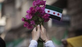 In this Friday, Sept. 21, 2012 photo, a Syrian woman holds a bouquet of flowers and rebel flag during a demonstration in the Bustan al-Qasr neighborhood of Aleppo, Syria. The Britain-based Syrian Observatory for Human Rights said Friday that nearly 30,000 Syrians have been killed during the 18-month uprising against the Assad regime. (AP Photo/ Manu Brabo)