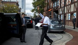 President Barack Obama walks from Usinger's Sausage to his car while eating bratwurst, Saturday, Sept. 22, 2012, in Milwaukee. (AP Photo/Carolyn Kaster)