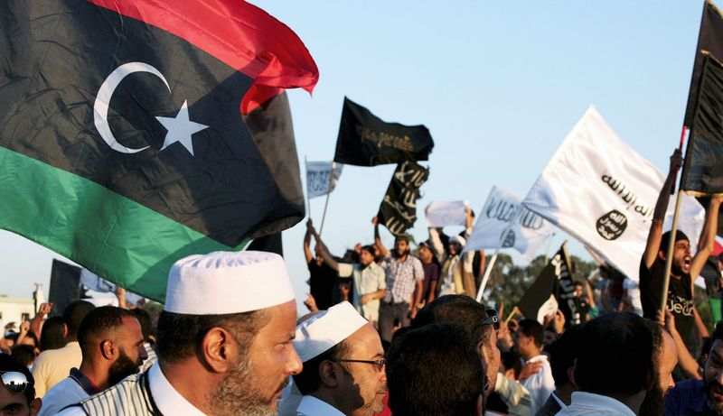 Libyans pass by a demonstration by Ansar al-Shariah and other Islamic militias (background) in a protest against the militias in Benghazi, Libya, on Friday. The compounds of several armed groups were stormed to demand that the groups disband. (Associated Press)