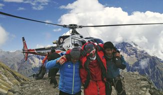 A mountain climber (center) injured in an avalanche is rescued at the base camp on Mount Manaslu in northern Nepal on Sunday, Sept. 23, 2012. The avalanche swept away climbers on a Himalayan peak and left at least nine dead and six others missing, officials said. (AP Photo/Simrik Air)