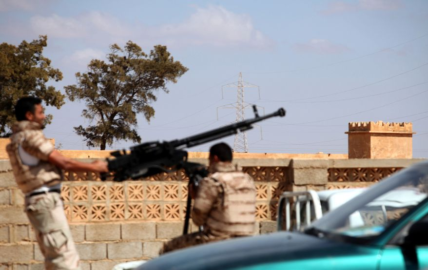 Soldiers from the Libyan National Army prepare to enter the Rafallah al-sahati Islamic Militia Brigade's compound, seen behind the wall, in Benghazi, Libya, on Saturday, Sept. 22, 2012. (AP Photo/Mohammad Hannon)