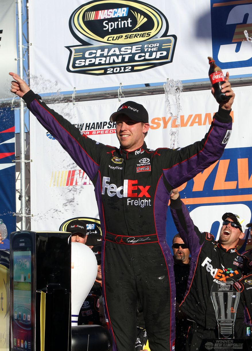 NASCAR driver Denny Hamlin celebrates with his team after winning the NASCAR Sprint Cup Series auto race at New Hampshire Motor, Speedway, Sunday, Sept. 23, 2012, in Loudon, N.H. (AP Photo/Jim Cole)