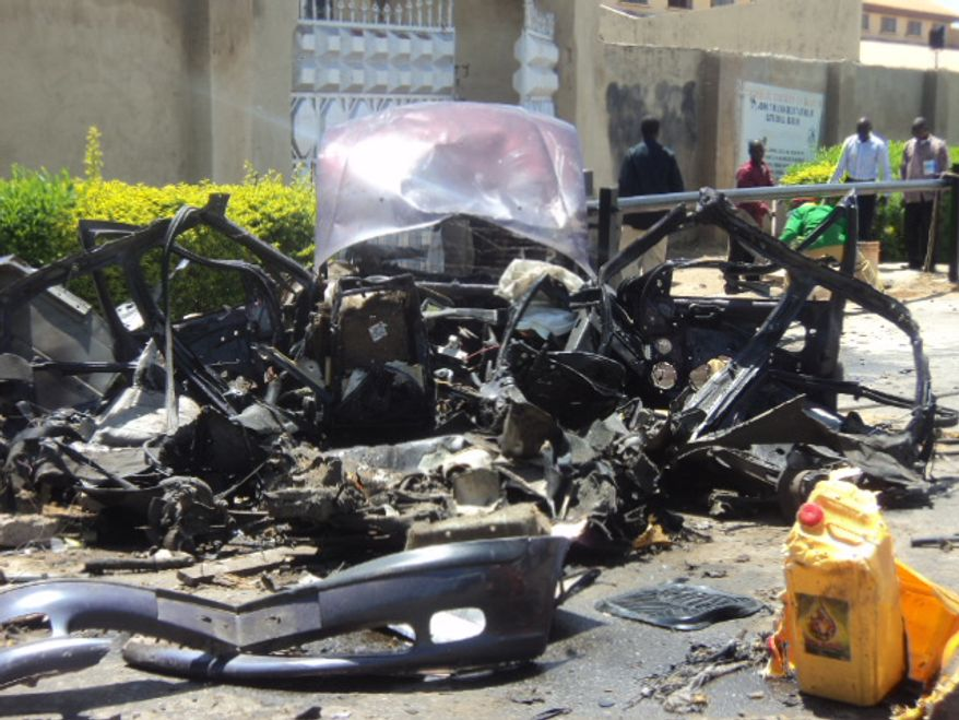 The remains of a car used in a suicide bombing sit outside a church in Bauchi, Nigeria, on Sunday, Sept. 23, 2012. The attack killed two people and wounded another 45, officials said. (AP Photo)