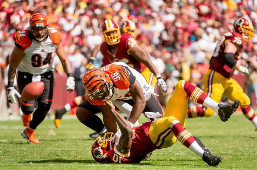Washington Redskins quarterback Robert Griffin III (10) fumbles after being hit by Cincinnati Bengals defensive end Carlos Dunlap (96) in the second quarter as the Washington Redskins play the Cincinnati Bengals on their home opener at FedEx Field, Landover, Md., Sunday, September 23, 2012. (Andrew Harnik/The Washington Times)