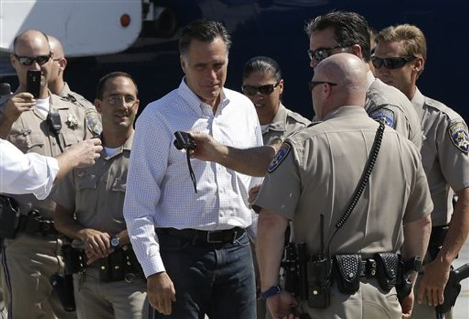 Republican presidential candidate Mitt Romney takes pictures with California Highway Patrol officers before he boards his campaign plane in Los Angeles on Sept. 23, 2012. (Associated Press)