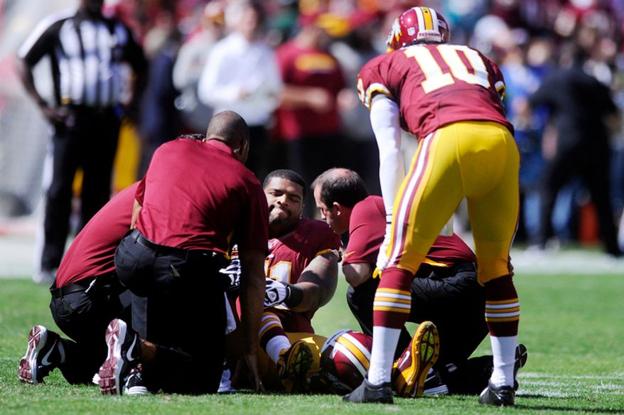 Washington Redskins tackle Trent Williams (71) sits injured on the field as quarterback Robert Griffin III (10) looks on at FedEx Field. (Preston Keres/Special to The Washington Times)