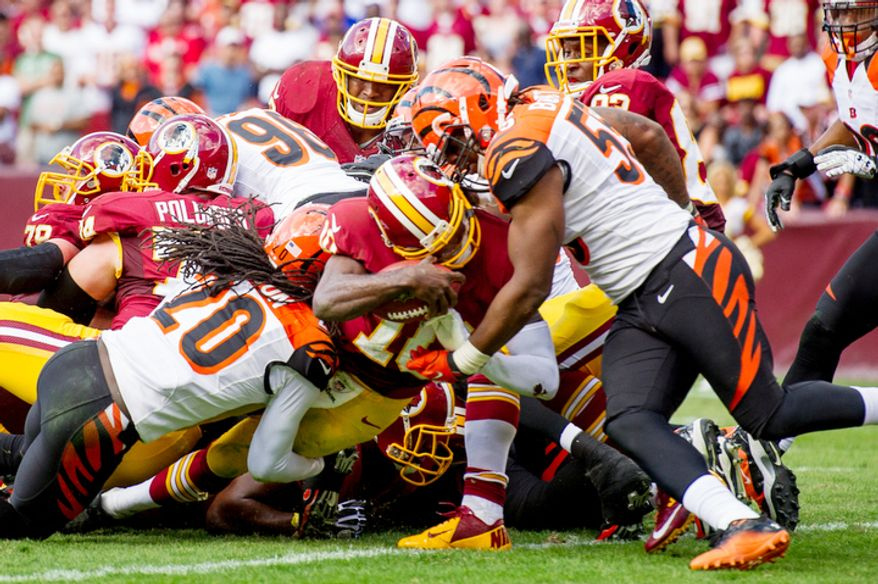 Washington Redskins quarterback Robert Griffin III (10) takes the ball in himself on a two yard running touchdown up the middle in the fourth quarter as the Washington Redskins lose to the Cincinnati Bengals 38-31on their home opener. (Andrew Harnik/The Washington Times)