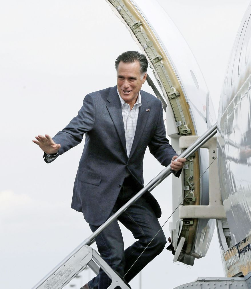 Mitt Romney boards his plane in Denver on Monday as he heads to another campaign stop. (Associated Press)