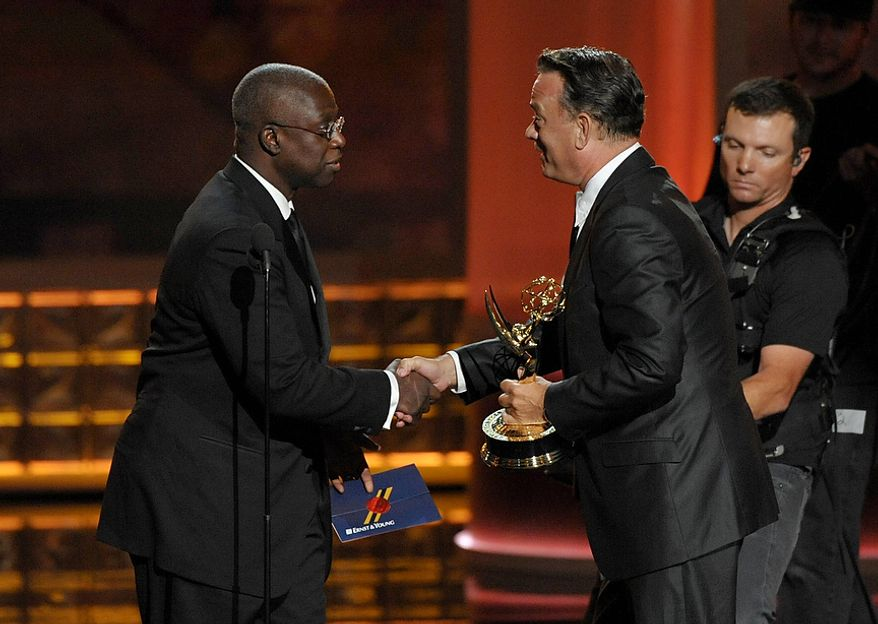 """Andre Braugher (left) presents the award for Outstanding Miniseries or Movie to Tom Hanks for """"Game Change"""" at the 64th Primetime Emmy Awards at the Nokia Theatre on Sunday, Sept. 23, 2012, in Los Angeles. (John Shearer/Invision/AP)"""